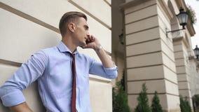 Młody człowiek opowiada na telefon pozyci na ulicie zbiory wideo