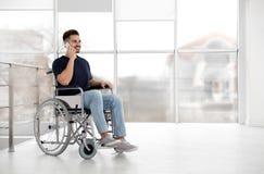 Młody człowiek opowiada na telefonie komórkowym blisko okno w wózku inwalidzkim fotografia royalty free