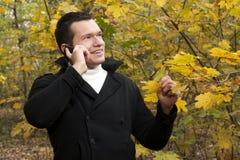 Młody człowiek opowiada na telefonie komórkowym przy parkiem zdjęcie royalty free