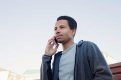 Młody człowiek opowiada na telefonie komórkowym w sport odzieży Facet outdoors Obrazy Royalty Free