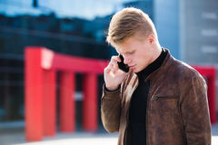 Młody człowiek opowiada na telefonie, używać smartphone, robi wezwaniu zdjęcia stock