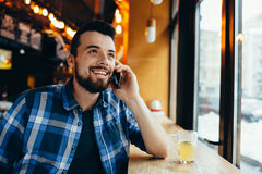 Młody człowiek opowiada na telefonie w kawiarni zdjęcie royalty free