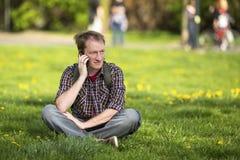 Młody człowiek opowiada na telefonu komórkowego obsiadaniu na zielonej trawie Fotografia Royalty Free