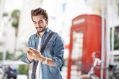 Młody człowiek opowiada telefon komórkowego w ulicie Zdjęcie Royalty Free