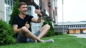 Młody człowiek opowiada w wideo gadce przez telefonu komórkowego, siedzący na trawie i mówi z przyjaciółmi zbiory