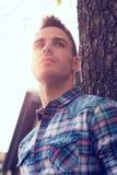 Młody człowiek outdoors przy zmierzchem, z słońcem za on zdjęcie stock
