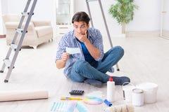 Młody człowiek overspending jego budżet w odnowienie projekcie zdjęcie stock