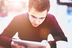 Młody człowiek pastylki studencki używa komputer w kawiarni Zdjęcia Royalty Free
