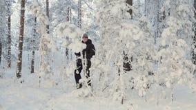 Młody człowiek patrzeje dla kierunku w zima śnieżnym lesie z smartphone zbiory