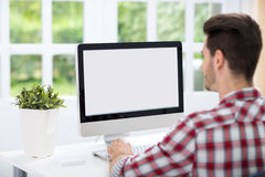 Młody człowiek patrzeje ekran komputerowego zdjęcia royalty free