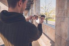Młody człowiek patrzeje go w łamanym lustrze Fotografia Royalty Free