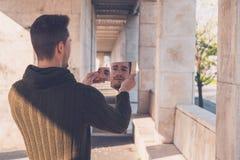 Młody człowiek patrzeje go w łamanym lustrze Obrazy Stock