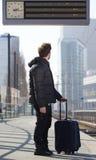 Młody człowiek patrzeje informacja znaka z torbą Zdjęcia Stock