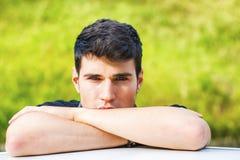 Młody człowiek patrzeje kamerę plenerową, opierający z Fotografia Royalty Free