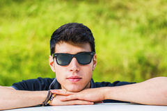 Młody człowiek patrzeje kamerę plenerową, opierający z Zdjęcie Royalty Free