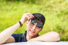Młody człowiek patrzeje kamerę plenerową, opierający z Fotografia Stock