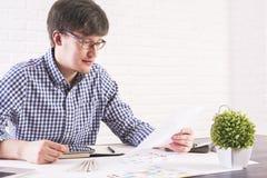 Młody człowiek patrzeje papier Zdjęcia Royalty Free