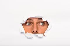Młody człowiek patrzeje przez papierowego rozprucia Zdjęcie Royalty Free