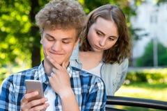 Młody człowiek patrzeje w telefon czyta wiadomość Facet z dziewczyną w lecie w naturze Dziewczyna szpieguje od zdjęcia stock