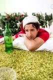 Młody człowiek pijący w domu po przyjęcia gwiazdkowego obraz royalty free