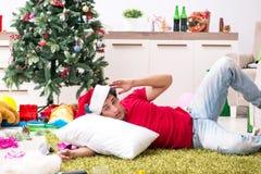 Młody człowiek pijący w domu po przyjęcia gwiazdkowego fotografia stock