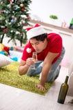 Młody człowiek pijący w domu po przyjęcia gwiazdkowego zdjęcie stock