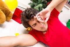 Młody człowiek pijący w domu po przyjęcia gwiazdkowego fotografia royalty free