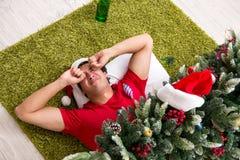 Młody człowiek pijący w domu po przyjęcia gwiazdkowego zdjęcie royalty free