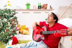 Młody człowiek pijący w domu po przyjęcia gwiazdkowego zdjęcia stock