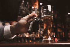 Młody człowiek pijący z szkłem piwo i klucz w jego ręce obrazy stock