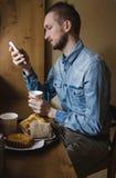 Młody człowiek pije kawę w kawiarni i używa telefon Obrazy Stock