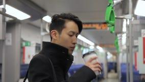 Młody człowiek pije kawę w poruszającym autobusie zbiory