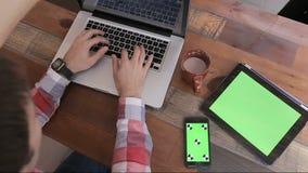 Młody człowiek pisać na maszynie na jego laptopie w kawiarni Pastylka z zieleń ekranem Smartphone dotyka ekran Z zieleń ekranu Ch zbiory wideo