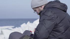Młody człowiek pisze puszkowi jego myślach w notatniku troszkę w ciepłym kurtki i kapeluszu obsiadaniu na lodowu niesamowita natu zdjęcie wideo