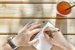 Młody człowiek pisze w jego notatniku Zdjęcie Stock