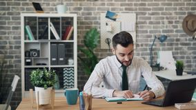 Młody człowiek pisze w notatniku i używa laptopu obsiadanie przy biurkiem w biurze zbiory