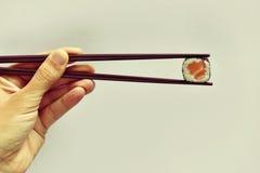 Młody człowiek podnosi makizushi z parą chopsticks Fotografia Stock