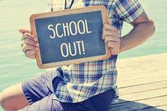 Młody człowiek pokazuje chalkboard z tekst szkołami out, z a Obraz Royalty Free