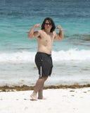 Młody człowiek pokazuje jego mięśnie na plaży Obrazy Royalty Free