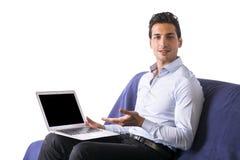 Młody człowiek pokazuje laptopu obsiadanie na leżance. fotografia stock