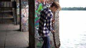Młody człowiek pozuje w frontowej kolorowej graffiti ścianie zbiory