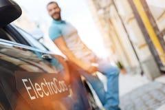 Młody człowiek pozycja blisko jego nowego elektrycznego samochodu obrazy royalty free