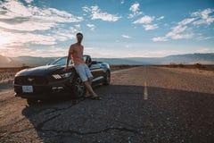 Młody człowiek pozycja czarnym Ford mustangiem GT obraz stock