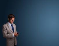 Młody człowiek pozycja i pisać na maszynie na jej telefonie z kopii przestrzenią Zdjęcie Stock