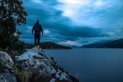 Młody człowiek pozycja na kamieniu blisko fjord przy nocą, Norwegia Obrazy Royalty Free