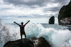 Młody człowiek pozycja na skale z morzem macha łamanie w frront fotografia stock