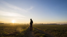 Młody człowiek pozycja na wiejskiej drodze w pięknym krajobrazowym spojrzeniu obraz royalty free