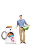 Młody człowiek pozycja pralką Fotografia Stock