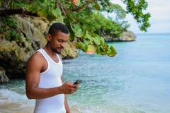 Młody człowiek pozycja przy plażą z telefonem w ręce gapi się przy telefonu ekranem obrazy royalty free