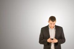 Młody człowiek pozycja texting na jego telefonie komórkowym Zdjęcia Royalty Free